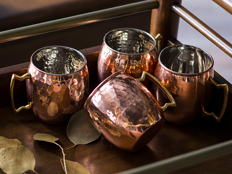 Close up shot of moscow mule mugs on a dining cart sprinkled with fall leaves