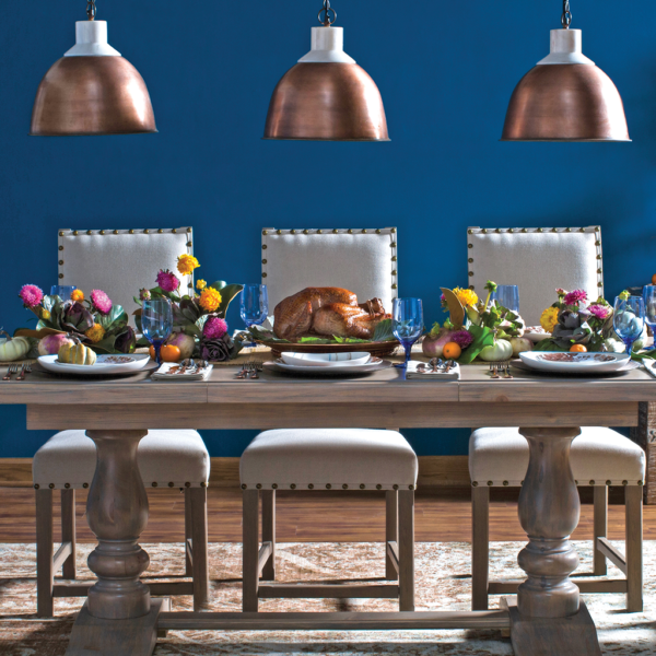 Long wood table with padded beige chairs, a turkey on a platter in the middle, pink/yellow/orange flowers on either side of the turkey, and 3 bronze pendant lights hanging overhead